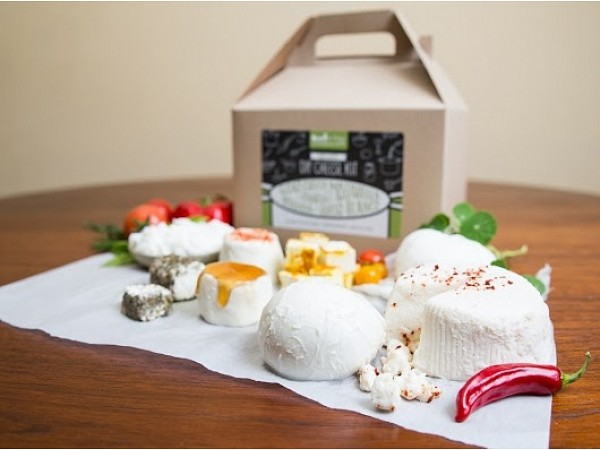 tan gift box with spread of luxury cheeses on a white cloth